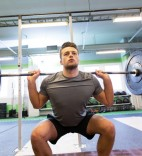 sport, fitness and bodybuilding concept - young man with barbell flexing muscles in gym